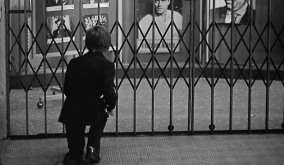 At night Ferrand has a dream, in black and white, in which he's a small boy going downtown after dark. He reaches through the grating in front of the local theater, and steals the 8-by-10 glossy publicity stills for Citizen Kane.